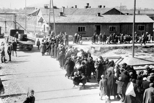 1280px-Birkenau_a_group_of_Jews_walking_towards_the_gas_chambers_and_crematoria.jpg